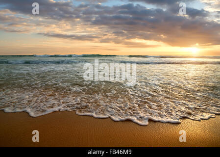 Bright cloudy sunset in the calm ocean - Stock Photo