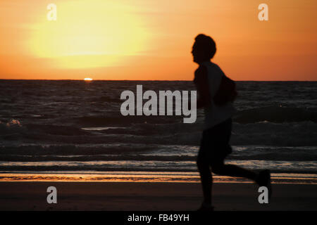 Runner at sunset on the beach at Cable Beach, Broome, Western Australia with bright orange sky backdrop - Stock Photo
