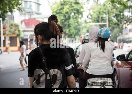 View of a busy street on a weekday in Hanoi, Vietnam. People are seen riding on motorbikes, cycles and cars  to - Stock Photo