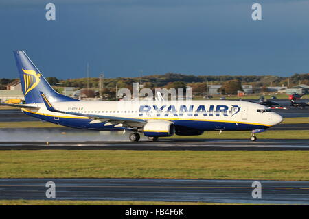 Ryanair's EI-EPH trundles down Prestwick Airport's main runway, leaving a trail of spray behind it. - Stock Photo