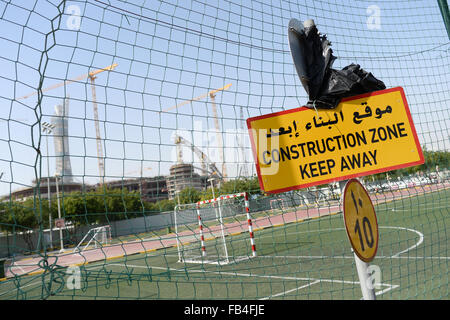 A sign reading 'Construction Zone - Keep Away' stands at an entrance to the construction site of the Khalifa International - Stock Photo