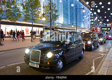 Christmas lights and London taxi cab driver waiting in traffic queue outside John Lewis Department Store in Oxford - Stock Photo