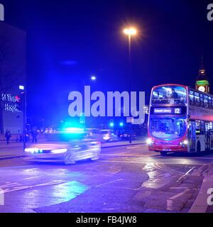 Metropolitan police car with blue flashing lights illuminating night sky on Westminster Bridge with london bus waiting - Stock Photo