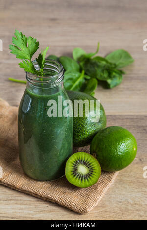 Green smoothie in a glass bottle with ingredients - Stock Photo