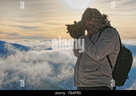 Man taking photos on top of Kasprowy Wierch of Zakopane in winter. Zakopane is a town in Poland in Tatra Mountains. - Stock Photo