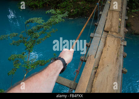 A tourist walks over a rickety bridge that crosses the milky blue water of the Rio Celeste, Costa Rica - Stock Photo