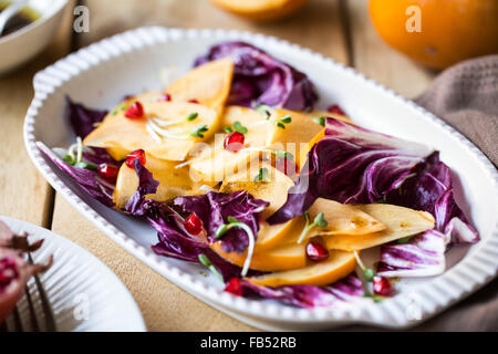 Persimmon with Radicchio and Pomegranate salad by Balsamic dressing - Stock Photo