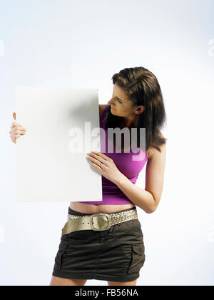 woman holding a card and looking at the side - Stock Photo