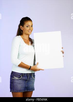 young woman holding a card facing camera - Stock Photo
