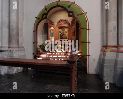 candles and pictures in the catholic Münster Basilica church in Bonn, Germany - Stock Photo