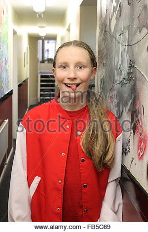 Cheeky young blond girl with her tongue stuck out wearing a red and white jacket. - Stock Photo