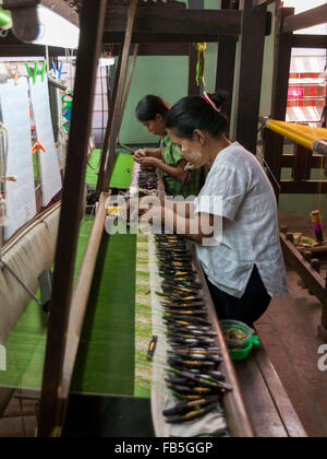 Two women weaving by using shuttles with thread spools on a loom. Partially woven green silk fabric visible. Mandalay, - Stock Photo