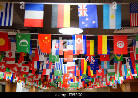 Many countries flags hanging from a ceiling on ropes - Stock Photo