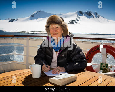 Antarctic, South Orkney Islands, tourist writing on rear deck of MS Hanseatic moored off Laurie Island coast - Stock Photo