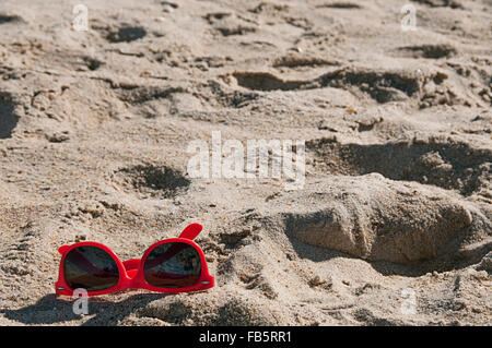 A pair of red sunglasses laying on the beach in the Outer Banks, North Carolina. - Stock Photo