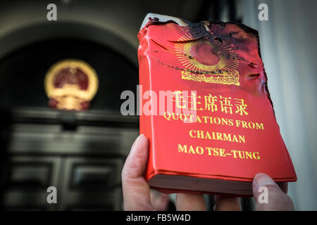 London, UK. 10th January, 2016. A protester holds up a partly burnt copy of 'Quotations from Chairman Mao Tse-tung' - Stock Photo