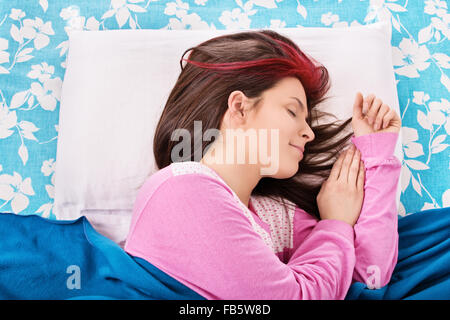 Sweet dreams. Beautiful young girl in pajamas calmly sleeping in her bed. - Stock Photo