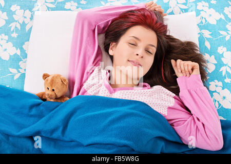 We're sleeping, my teddy bear and I. Beautiful young girl in bed, sleeping with her teddy bear. - Stock Photo