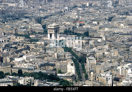 An aerial photograph shows the towering Arc de Triomphe standing out amid the many buildings and tree-lined boulevards - Stock Photo