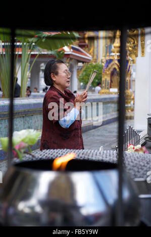 BANGKOK, THAILAND - OCTOBER 26, 2014: Thai woman prays at a Buddhist shrine in front of the Temple of the Emerald - Stock Photo