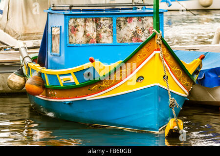 Traditional Luzzu boat at Marsaxlokk harbor, a fishing village located in the south-eastern part of Malta - Stock Photo