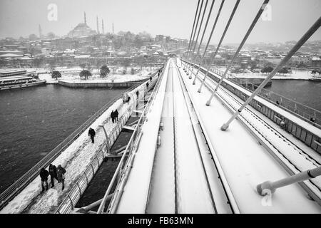 People walking on the Golden Horn Metro Bridge on a snowy day, 2016. - Stock Photo