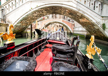 View from gondola trip during the ride through the narrow canals with many bridges in Venice Italy - Stock Photo