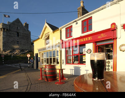 A pint of Guinness at sunset outside Bushe's Bar in Baltimore, West Cork, Ireland - Stock Photo