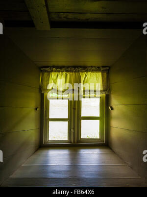 Historic Turf house close up interior closed window with a yellow green window valance curtains, Iceland, Europe, - Stock Photo