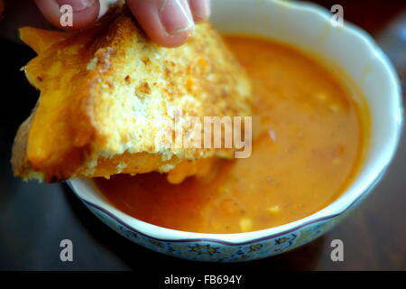Hand holding a grilled cheese sandwich dipped in a bowl of creamy tomato soup - Stock Photo