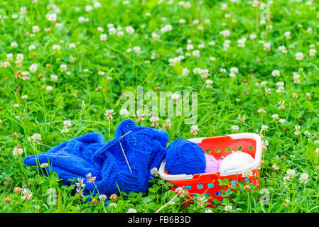 basket with skeins of wool and knitting on the green grass - Stock Photo