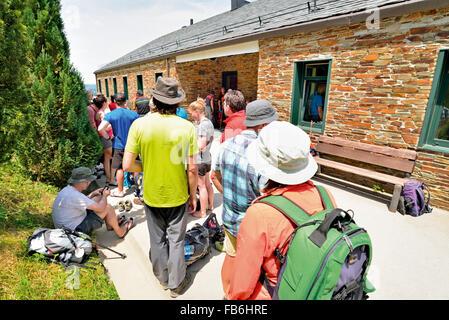 Spain, St.James Way: Pilgrims waiting to enter in the Pilgrim´s Hostel in O Cebreiro - Stock Photo