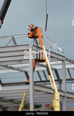 Construction work in the UK : Men working at height on elevated 'cherry picker' platforms,  bolting together the - Stock Photo