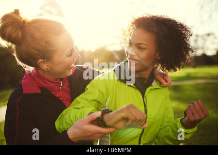 Two female athletes smiling and hugging after workout in sunny park - Stock Photo