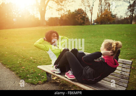 Two female athletes doing sit-ups on bench in park - Stock Photo
