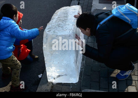 Beijing, China. 9th Jan, 2015. People watch an ice brick got from a lake at Shichahai, a scenic area in Beijing, - Stock Photo