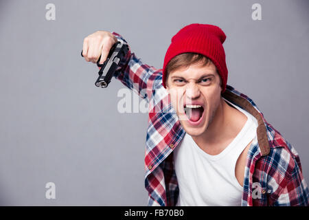 Dangerous agressive young man in checkered shirt and red hat shouting and threatening with gun over grey background - Stock Photo