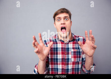 Portrait of terrified frightened young man in checkered shirt screaming with open mouth over grey background - Stock Photo
