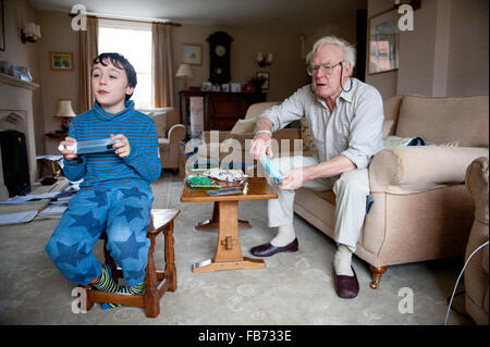 11 year old grandson playing on the wii with his grandfather in North Yorkshire - Stock Photo