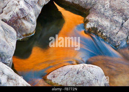 Red glowing rock wall reflecting in Ormiston Creek. - Stock Photo