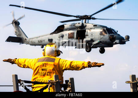 Sikorsky MH-60 Seahawk helicopter, U.S. Navy Petty Officer 3rd Class signals an MH-60S Seahawk helicopter - Stock Photo