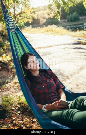 Young hiker resting on hammock in forest - Stock Photo