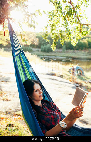 Young woman reading book while lying on hammock in forest - Stock Photo