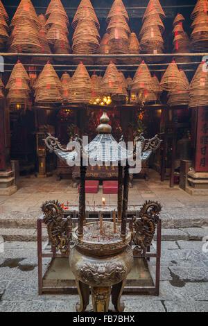 Urn with burning incense sticks and incense cones at the Man Mo Temple in Tai Po, Hong Kong, China. - Stock Photo