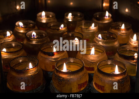 Close-up of several burning candles in dirty glass jars - Stock Photo