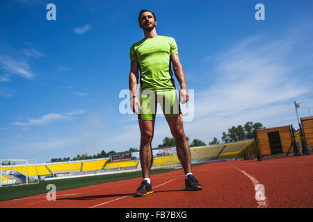 Full length of determined male athlete standing on race track - Stock Photo