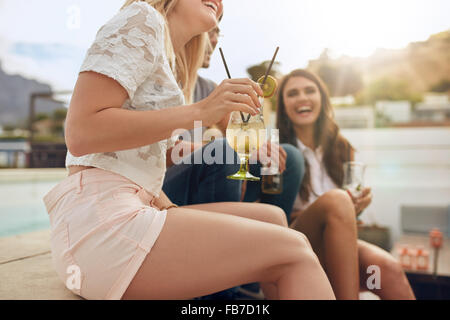 Cropped shot of young people sitting together hanging out with drinks. Partying on rooftop with focus on cocktail - Stock Photo