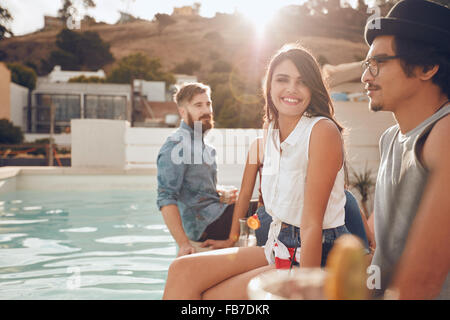 Portrait of beautiful young woman sitting by the pool with her friends around partying. Group of young people hanging - Stock Photo
