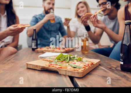 Close up shot of pizza on wooden plate with people eating and drinking in background. Group of friends gathered - Stock Photo