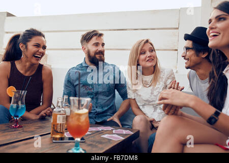 Group of friends relaxing together around a table. Young people hanging out around a table during a party with cocktails - Stock Photo